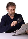 Elderly man reads a newspaper — Stock Photo