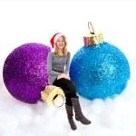 Girl sitting on Christmas balls — Stock Photo