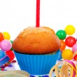 Birthday cupcake with candle streamers and colorful confetti — Stock Photo