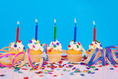 Birthday cupcakes with candle streamers and colorful confetti — Stock Photo