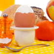 Breakfast with peeled egg, delicious bread and fruits - Stock Photo