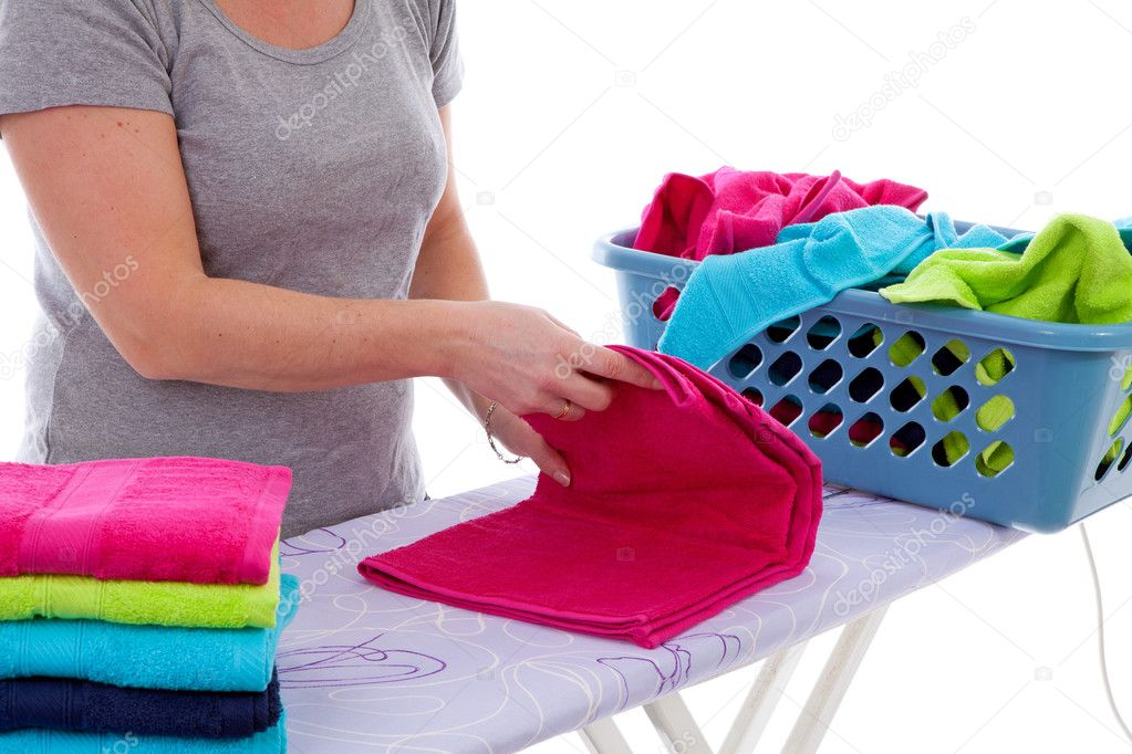 Housewife is folding colorful towels in closeup over white background — Stock Photo #9458609