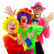 Three dressed up as colorful funny clowns — Stock Photo