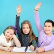 Three happy girls doing their school work — Stock fotografie #10352077