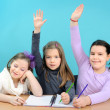 Three happy girls doing their school work — Stockfoto #10352077