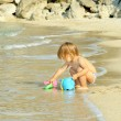 Stock Photo: Happy toddler girl playing with her bucket at the beach
