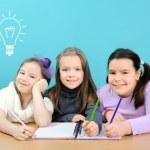 Happy school girls doing their work in classroom — Stock Photo
