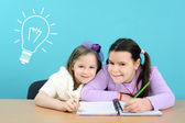 Two happy girls doing their school work — Stok fotoğraf