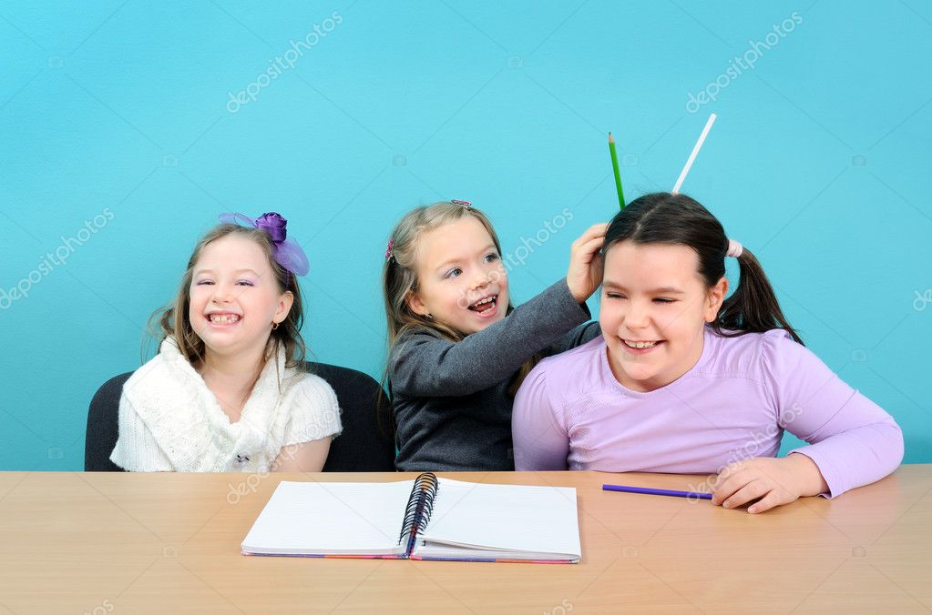 Three happy school girls making jokes in classroom — Stock Photo #10608352
