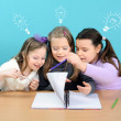 Three happy girls doing their school work — Stock Photo