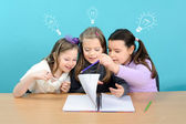 Three happy girls doing their school work — Stockfoto