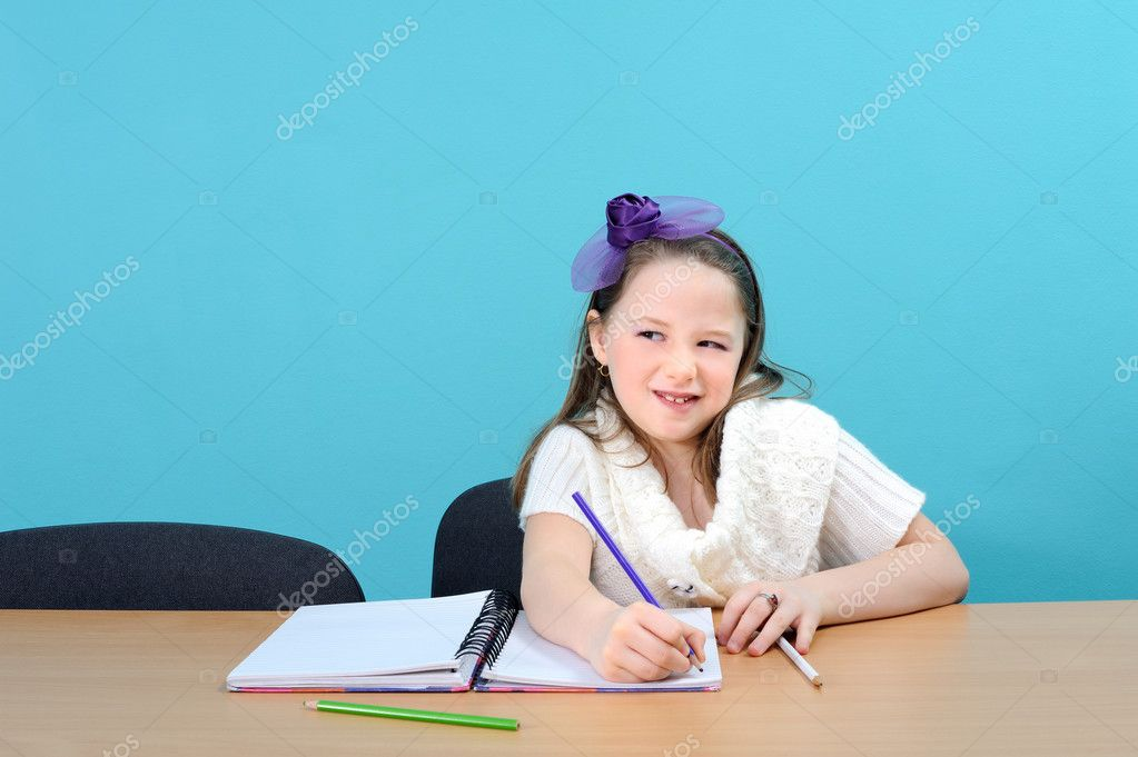 Adorable smiling girl doing her school work  Stock Photo #10641353