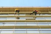 Washers wash the glass facade of modern skyscraper — Stock Photo