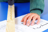 Carpenter`s hand with blueprints and drill machine — Stock Photo