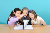Three happy girls doing their school work — 图库照片