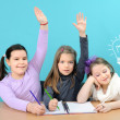 Foto Stock: Three happy girls doing their school work