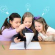 Three happy girls doing their school work — Stock Photo #8664856
