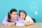 Two happy girls doing their school work — Photo