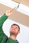 Electrician fixing ceiling light — Stock Photo
