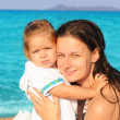 Happy child with her mother on the beach — Stock Photo