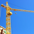 Royalty-Free Stock Photo: High-rise construction crane near the house under construction.