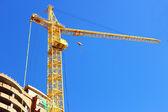 High-rise construction crane near the house under construction. — Stock Photo