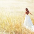 Woman walking in the sunny meadow on summer day touching grass — Stock Photo #8895035