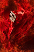 Beautiful woman in red waving silk dress as a fire flame. — Stock Photo