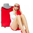 Beautiful woman sitting next to red suitcase and talking on phon — Stock Photo #9249714