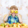 Happy boy playing with apples with fruits. — Stock Photo