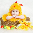 Baby in Easter basket with eggs in chicken costume — Stock Photo #9347180