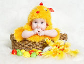 Baby in Easter basket with eggs in chicken costume — Stock Photo