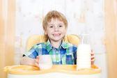 Child drinking milk. Holding glass of milk — Stock Photo