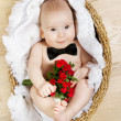 Adorable baby holding flowers and wearing butterfly tie, lying i — Stock Photo