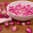 Fresh bright pink roses, petals, candle, and towel in a spa - Stock Photo