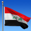 Flag of Iraq against blue sky. - Stock Photo