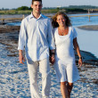 Young couple walking on beach — Stock Photo #9204985