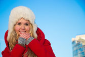 Portrait of woman in red coat blue backgound — Stock Photo