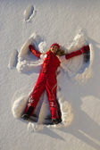Woman making an angel on snow — Stock Photo