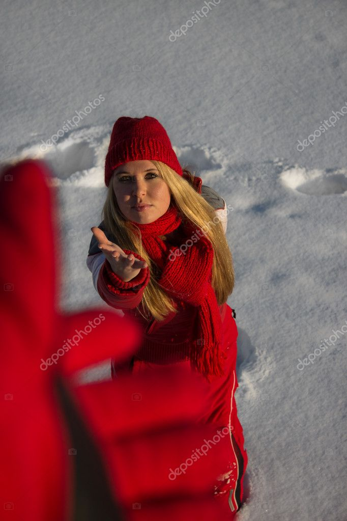 Young blond woman in red sport wear reaching out hand for help in winter — Stock Photo #8869357