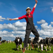 Happy farmer in field with cows - Stock Photo