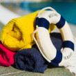 Towels and life buoy at swimming pool - Stock Photo