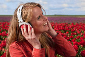 Dutch blond girl with headphones in field with tulips — Stock Photo