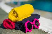 Serviettes de bain et lunettes de soleil à la piscine — Photo