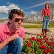 Young couple in flower fields — Stock Photo