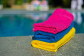 Colorful towels near swimming pool — Stock Photo