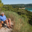 Man with dog sitting in French landscape — Stock Photo