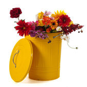 Yellow trash can with flowers — Stock Photo