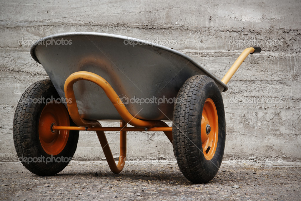 Orange farmer's two wheelbarrow on concrete background — Stock Photo #10277190