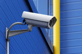 Surveillance camera next to yellow pipe — Stock Photo